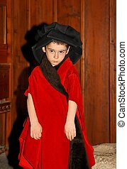 Serious cute little boy in medieval costume standing on wooden background