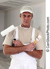 Serious decorator with a paintbrush and roller