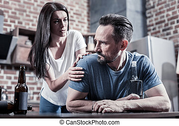 Serious depressed man listening to his wife