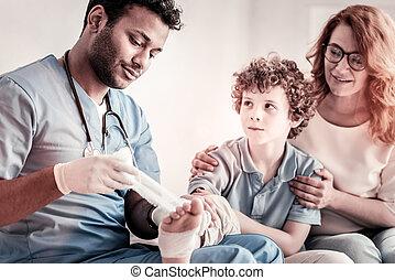 Serious doctor applying bandage on teen foot