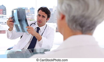 Serious doctor holding an x-ray in front of his patient in...
