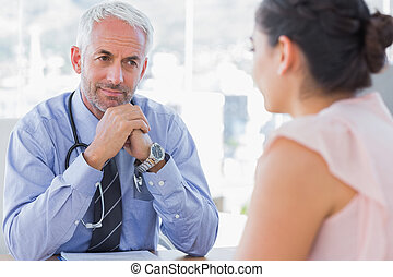 Serious doctor listening to patient explaining her painful