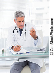 Serious doctor looking a medication for a prescription