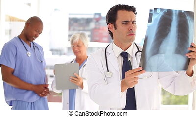 Serious doctor looking at a chest x-ray while standing in a...