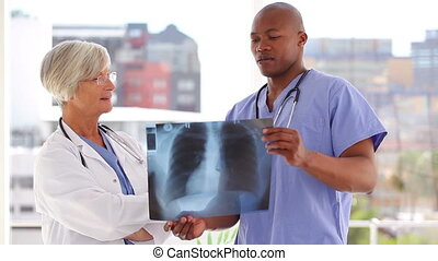 Serious doctor looking at an x-ray with a nurse