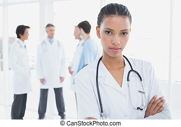 Serious doctor looking at camera with colleagues behind her