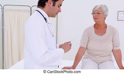 Serious doctor preparing a hypodermic needle