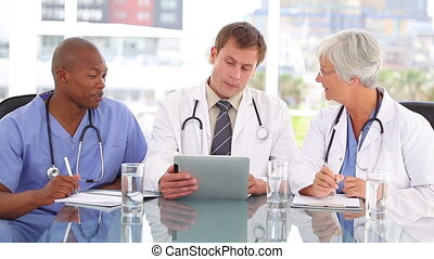 Serious doctor talking with his colleagues about a tablet pc