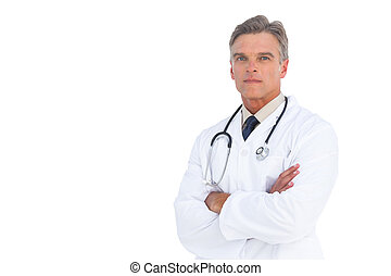 Serious doctor with arms crossed on white background