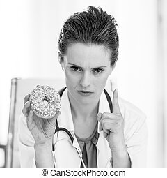 Serious doctor woman with donut threatening with finger