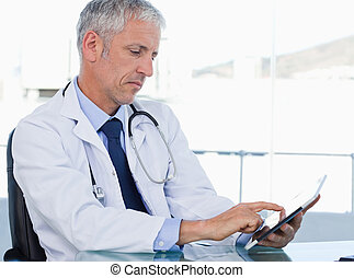 Serious doctor working with a tablet computer