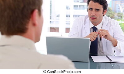 Serious doctor writing a prescription for his patient in a bright office