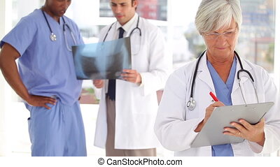 Serious doctor writing on a clipboard in front of her team...