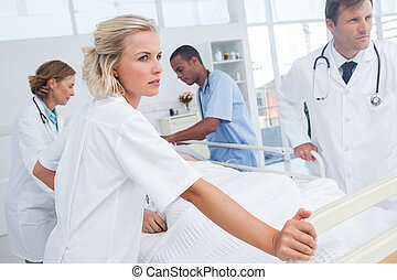 Serious doctors about to walk with patient bed