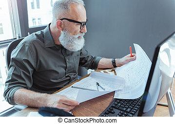 Serious elderly engineer is working in office