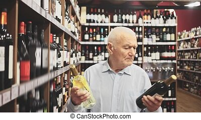 Serious elderly man chooses between red and white wine in a liquor store. High quality FullHD footage