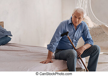 Serious elderly man sitting alone in the room