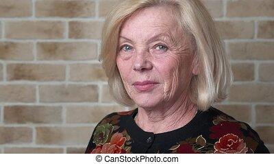 Serious elderly woman - Serious mature woman, brick wall...