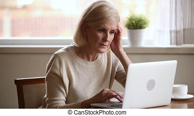 Serious elderly woman typing on computer working at home -...