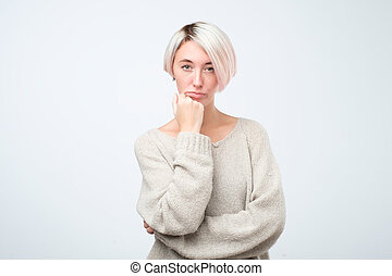 Serious european woman in gray sweater standing with crossed arms