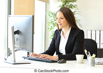 Serious executive is using a computer at office - Serious ...