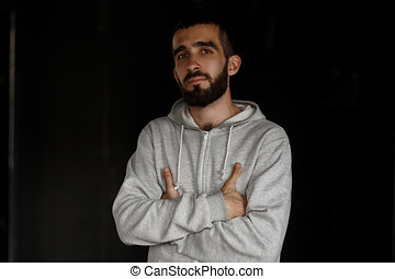 Serious face. Handsome business young man with a beard in a gray sweatshirt standing on a black background