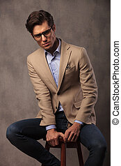 serious fashion model posing seated in studio