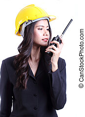 Serious female construction worker talking with a walkie talkie and orders to stop