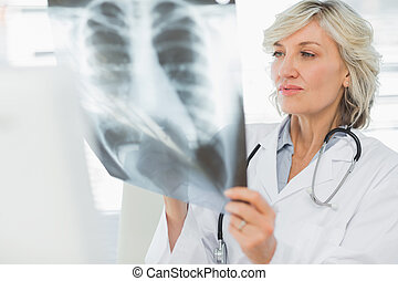 Serious female doctor examining x-ray