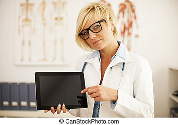Serious female doctor pointing at digital tablet