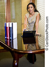 Serious female Hispanic office worker using laptop