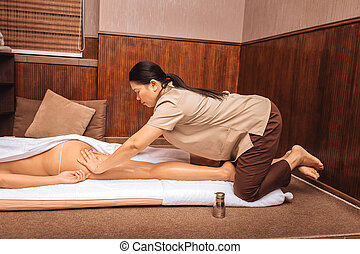 Serious female masseuse massaging her clients body