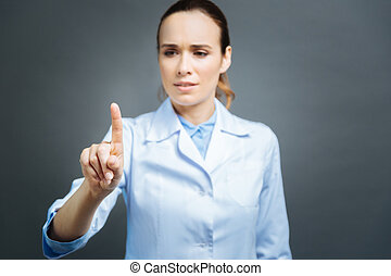 Serious female practitioner touching invisible screen