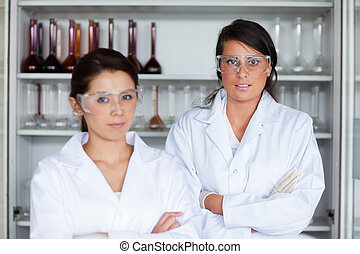 Serious female science students posing