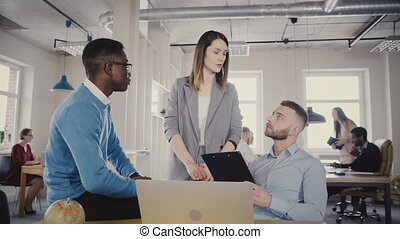 Serious female team leader talks to multiethnic employees, walks away. Workers agree with boss in modern loft office 4K.