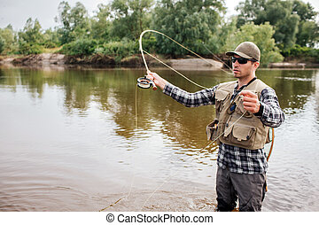 Serious fisherman stands on shallow an waving with fly-fishing. Also he has a spoon in other hand. Guy is looking to the left. He is concentrated.