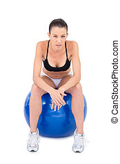 Serious fit woman sitting on exercise ball
