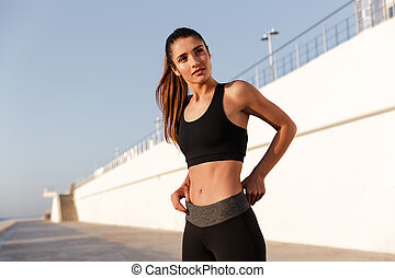 Serious fitness lady with beautiful healthy body looking camera