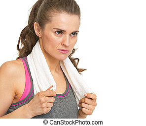 Serious fitness young woman with towel looking on copy space