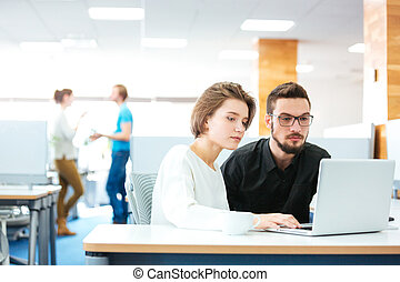 Serious focused man and woman working with laptop in office