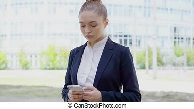 Serious formal woman browsing smartphone - Young serious...