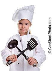 Serious girl chef white uniform isolated on white background. Holding black ladle and scapula crossed. Portrait image