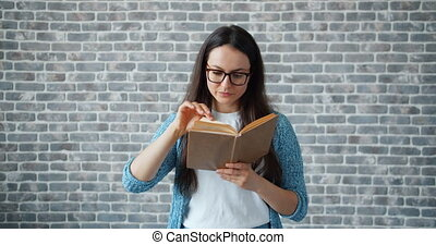 Serious girl in glasses reading book turning page on brick wall background