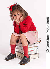 Serious girl sitting on books