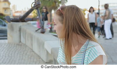 Serious girl thinking in a city embankment sitting