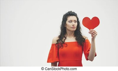 Serious girl with origami red heart. Valentine's Day. Good holidays Concept of celebration of love. Young and beautiful girl.