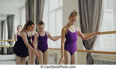 Serious girls are practising arm movements during ballet...
