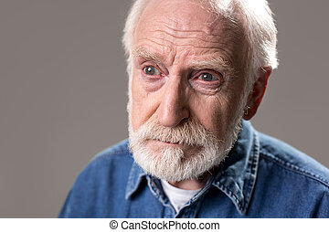 Serious grandfather getting lost in thought - Portrait of...