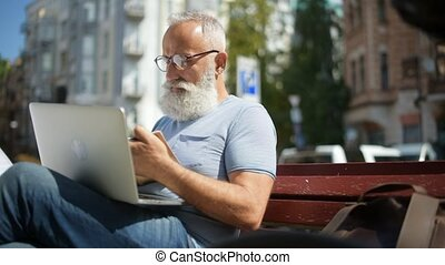 Serious greyheaired man making notes while sitting on bench