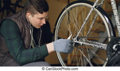 Serious guy experienced master is fixing bicycle wheel...
